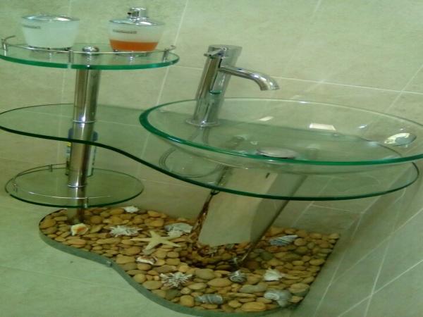 como elemento decorativo lavabo de cristal templado, con piedrs de río y cochas de mar, grifeía moderna.